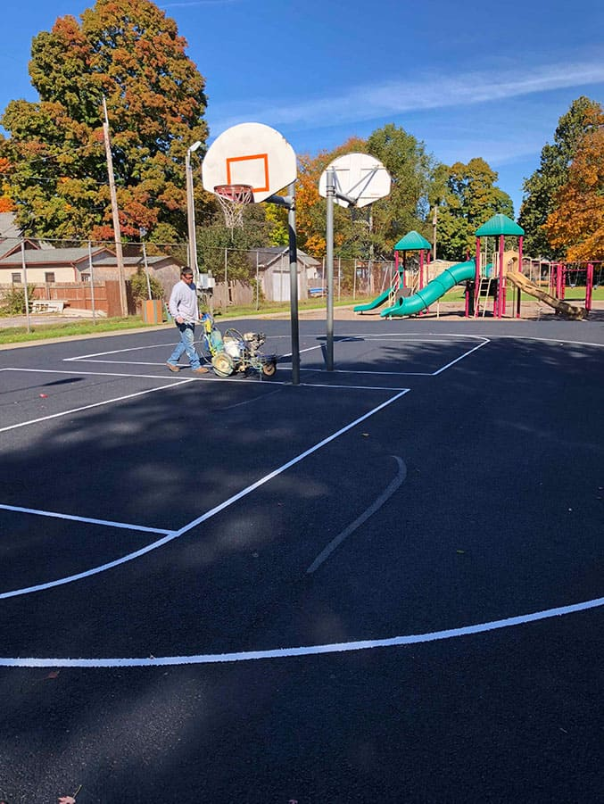 A Pro Drive employee resurfacing (patching and milling) a basketball court.