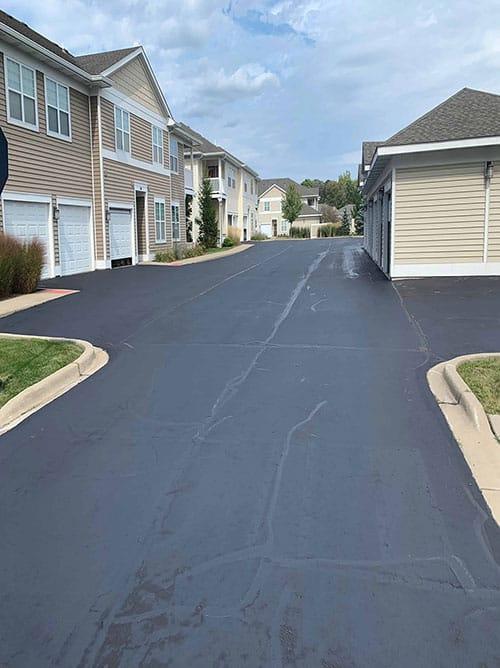 Asphalt professional crack filling resurfacing between houses in neighbourhood